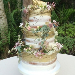 Semi frosted naked wedding cake with brushed gold